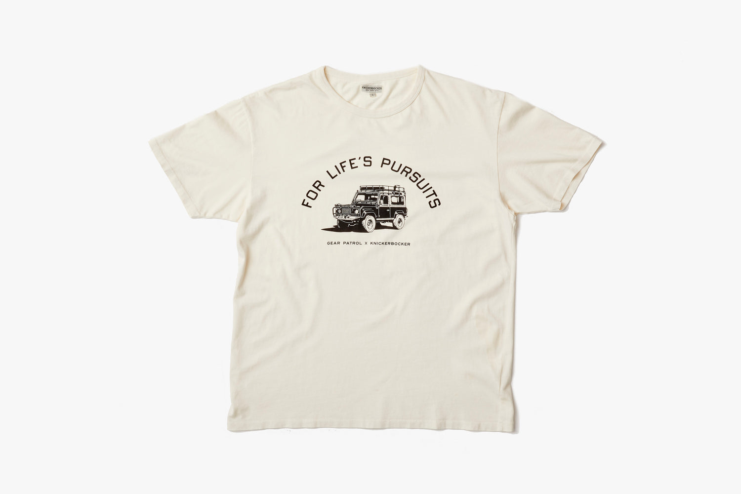 "Knickerbocker x Gear Patrol Overland T-Shirt - image of an off-white tee shirt showing an illustration of a Land Rover with ""For Life's Pursuits"" written above it"