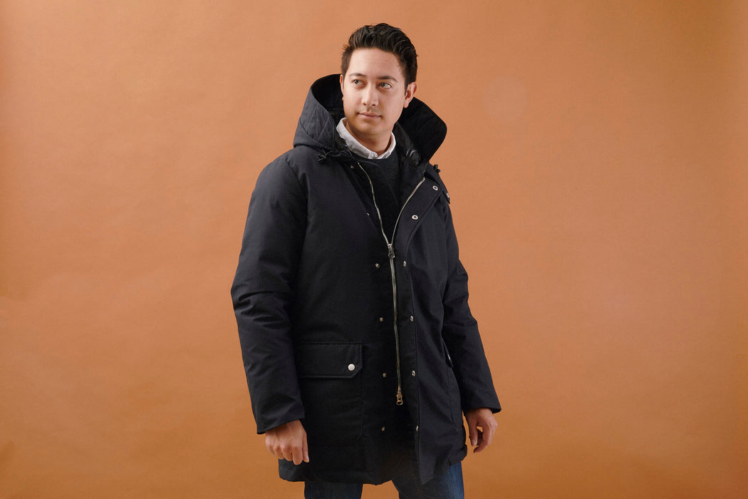 Black American Trench x Gear Patrol Parka - man looking to the side while wearing parka, mid-stride