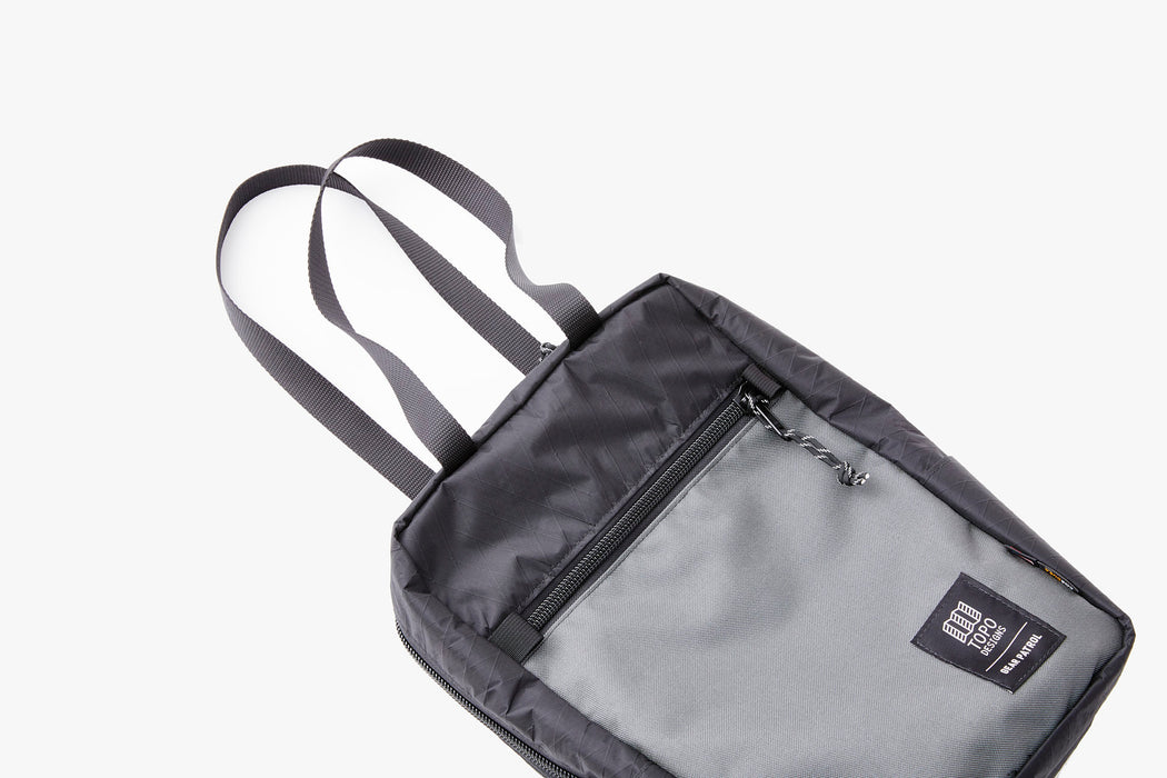Black/Grey - Topo Designs x Gear Patrol Backpack Tote - Front with bag laying down and tote straps out.