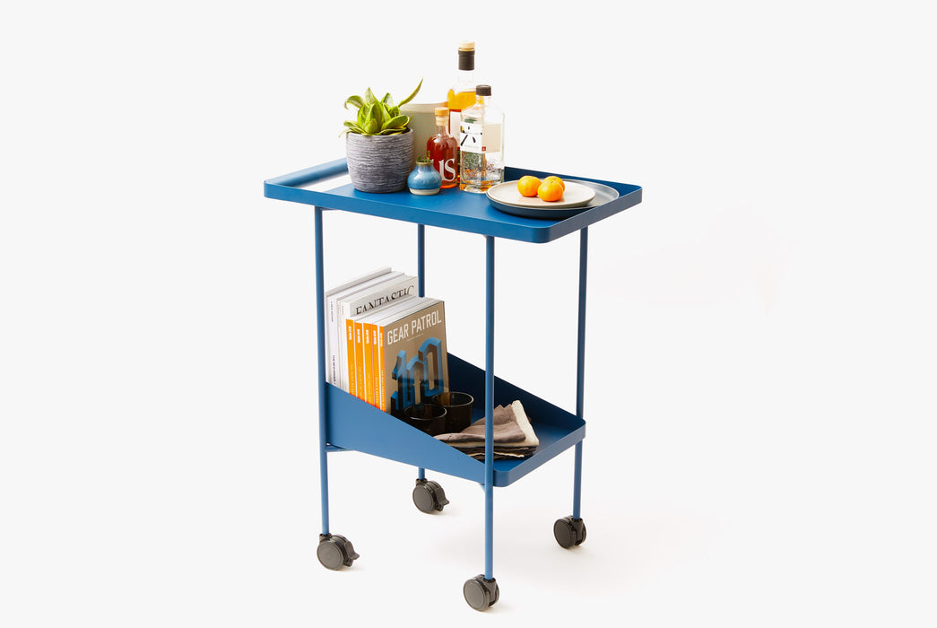 Blue Utility Cart Standing Up - Side View - Bottles, Fruit, and Plant on Top Shelf - Magazines, Glasses, Napkins on Bottom Shelf