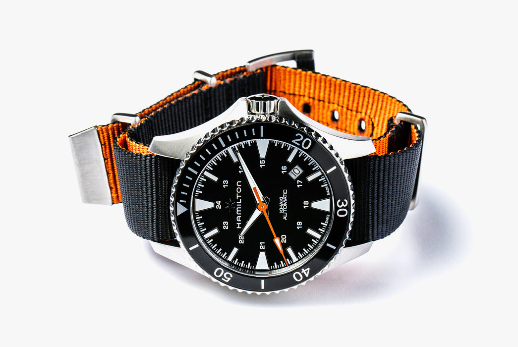 Hamilton Khaki Navy Scuba Auto - Special Edition - image of watch on its side with silver hardware, a black bezel, and orange and black strap