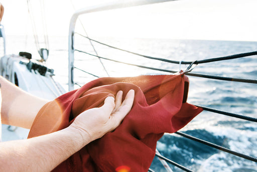 Matador NanoDry Towel Large - Rust - Person drying their hands on the towel while on a boat deck