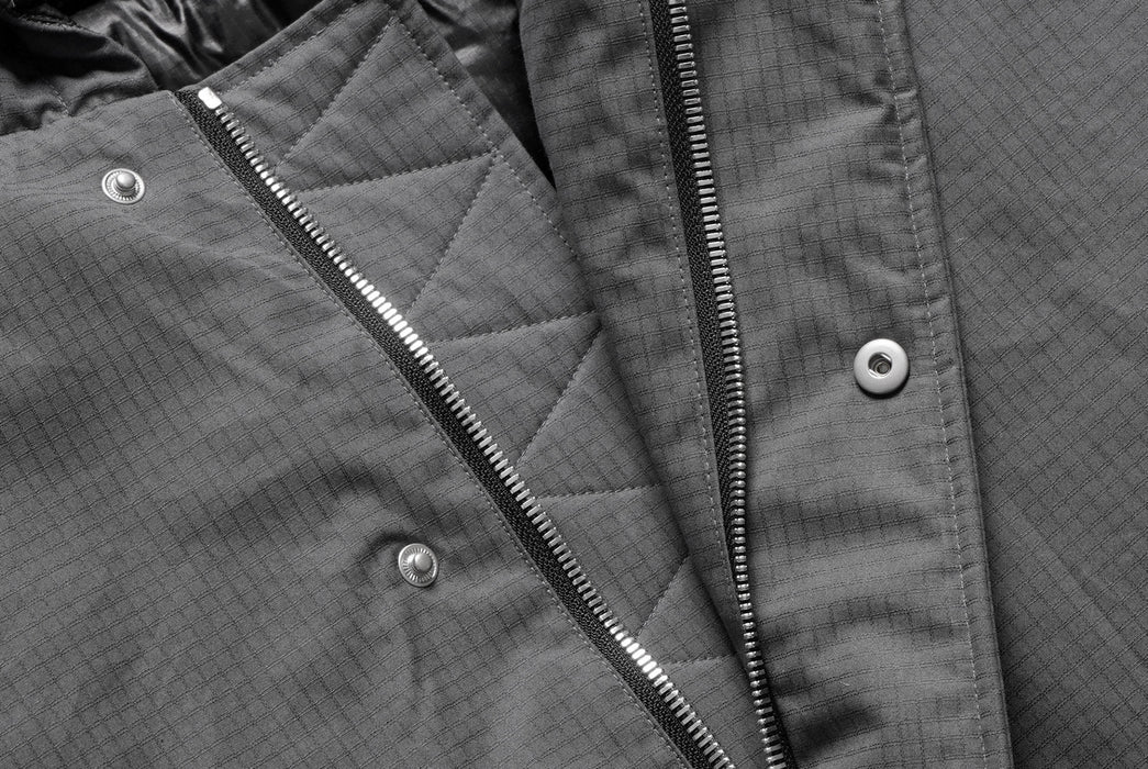Gray American Trench x Gear Patrol Parka - close-up on button and zipper detail on parka