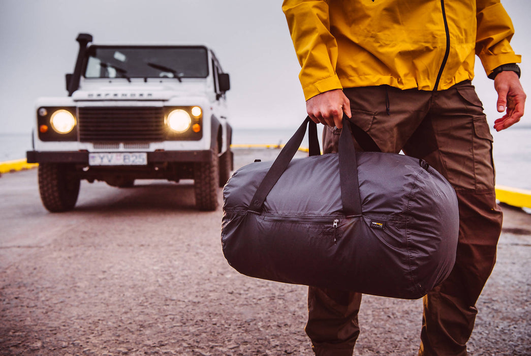 Matador Transit30 2.0 Duffel Bag - Black - Man holding duffel bag as he walks away from a Land Rover