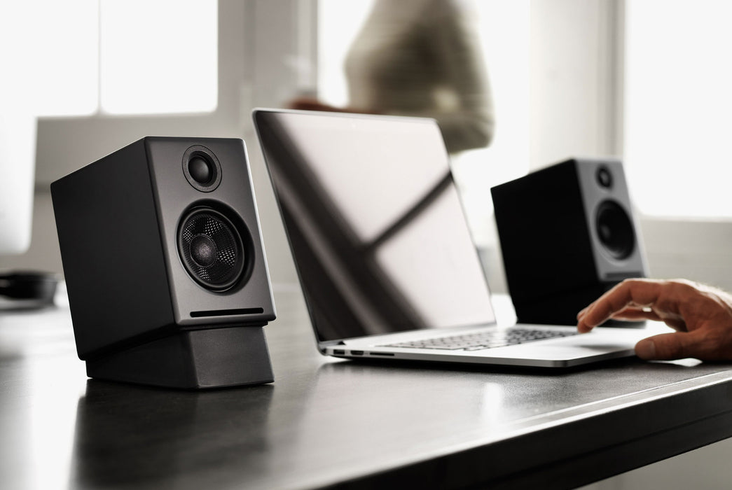 Black Speakers Beside Laptop with Model's Hand