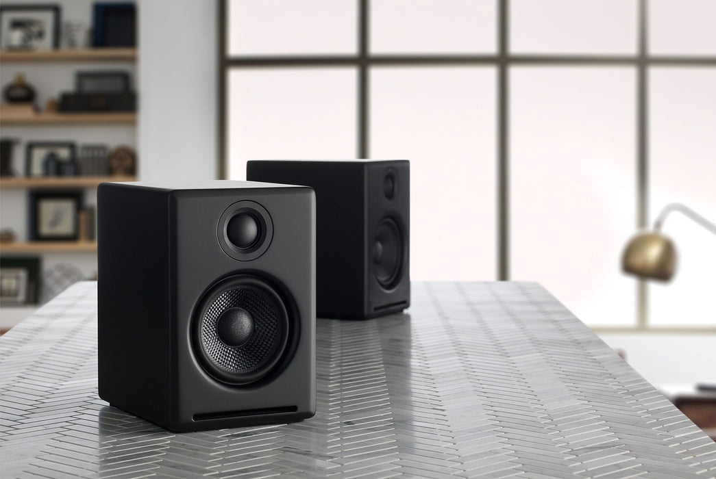Black Speakers Standing Up on Table - Side View