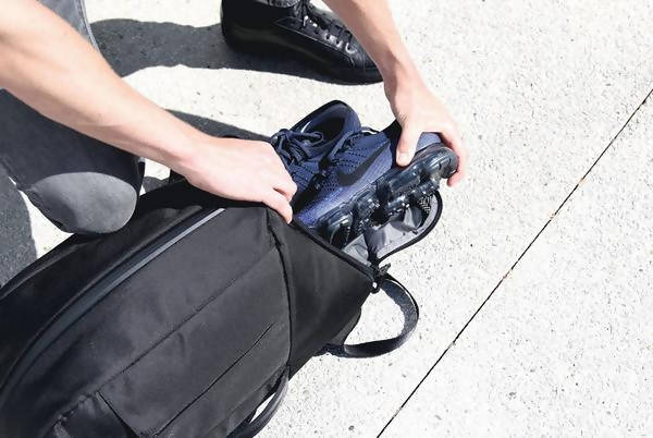 Black Duffel Pack - Lifestyle Shot of Model Pulling Sneakers out of Shoe Compartment