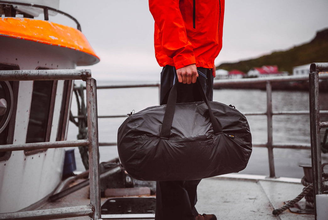 Matador Transit30 2.0 Duffel Bag - Black - Man holding duffel bag on a boat deck