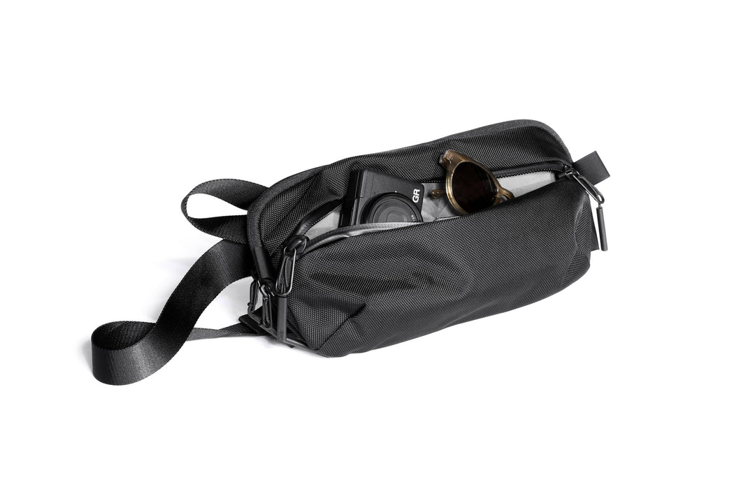 Black Sling Bag Standing Up - Unzipped Front Compartment with Camera and Sunglasses Pictured