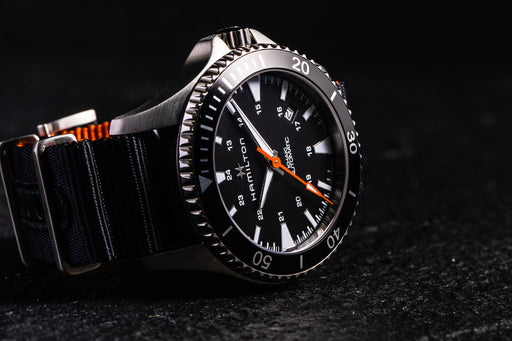 Hamilton Khaki Navy Scuba Auto - Special Edition - image of watch on its side showing black bezel, orange second hand, and black strap