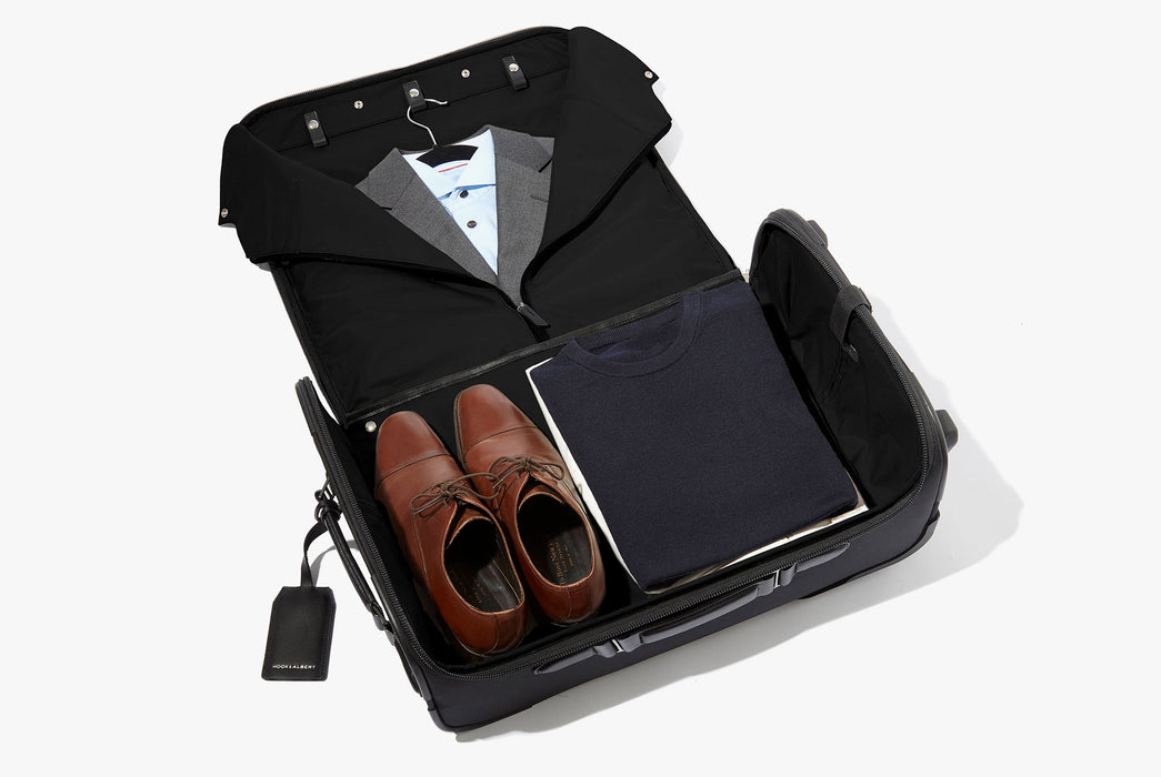 Hook & Albert Garment Luggage Carry-On Bag - bag unzipped showing a suit on a hanger, pair of shoes, and sweaters folded inside bag