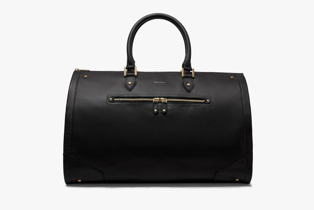 Hook & Albert Women's Black Leather Garment Weekender Bag - side view of bag standing up with handle extended and showing gold detailing