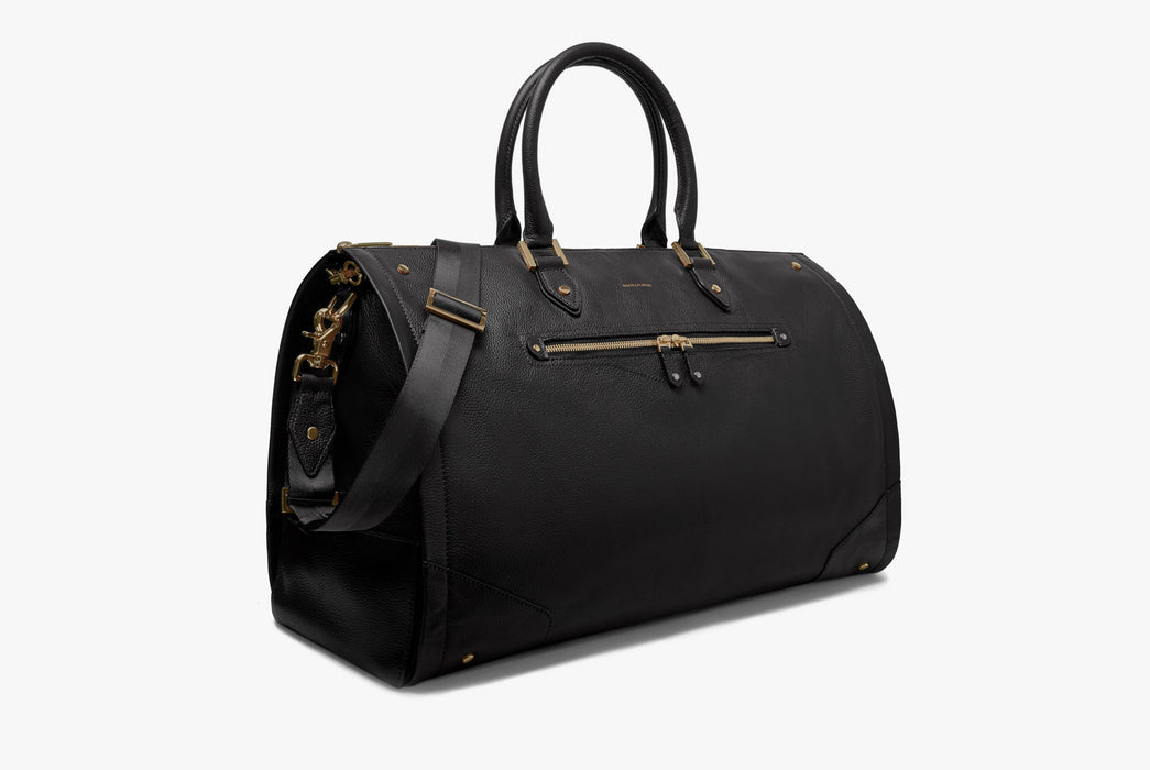 Hook & Albert Women's Black Leather Garment Weekender Bag - side view of bag standing up showing gold detailing and crossbody handle