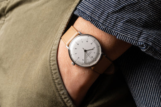 Junghans Max Bill Handwound Watch - man wearing watch, showing version with white dial, black numbers, and brown leather strap