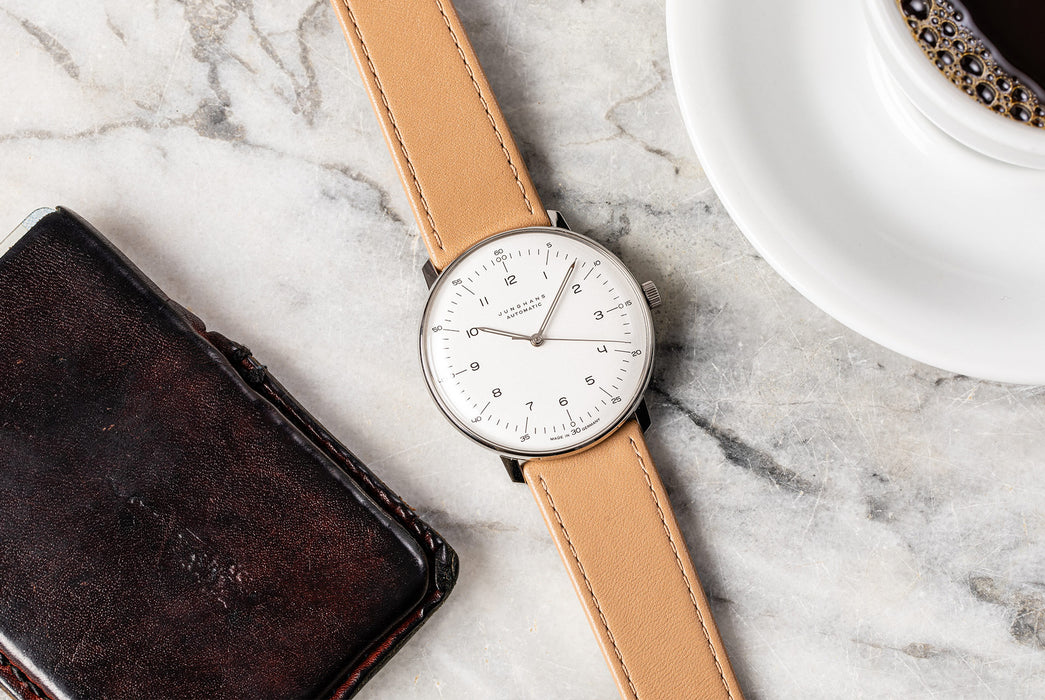 Junghans Max Bill Automatic Watch - watch laying down on a marble table, showing option with white dial and brown leather strap