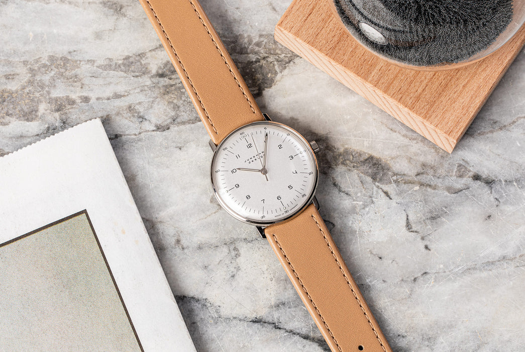 Junghans Max Bill Handwound Watch - watch on a marble table, showing version with white dial, black numbers, and brown leather strap