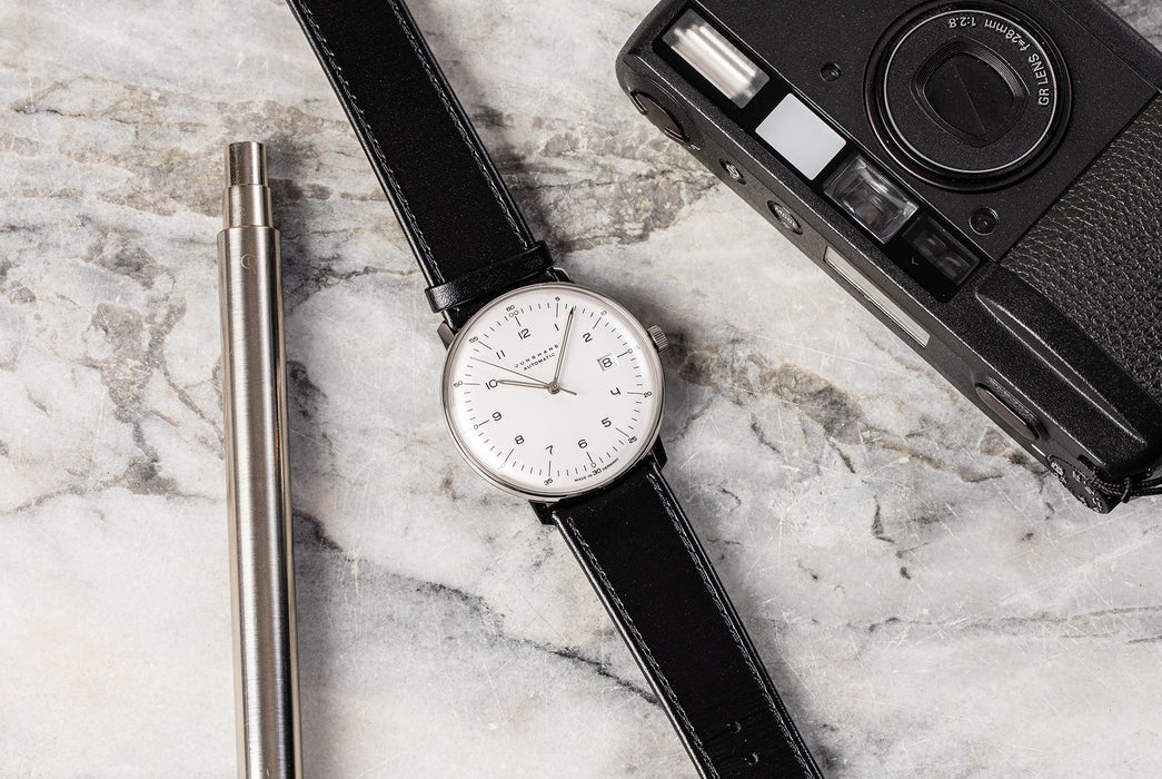 Junghans Max Bill Automatic Date Watch - watch on a marble surface next to a silver pen and vintage camera, showing option with a white dial and black leather strap