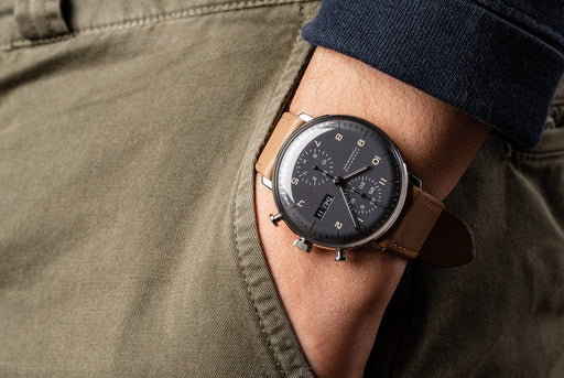 Junghans Max Bill Chronoscope Watch - watch on a man's wrist, showing version of gray dial and brown leather strap