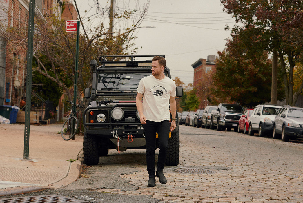 Knickerbocker x Gear Patrol Overland T-Shirt - image of a man, walking on a cobblestone street, wearing the Overland tee shirt