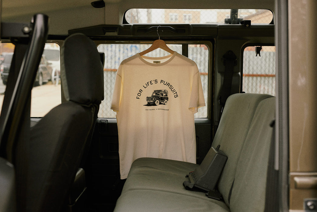 Knickerbocker x Gear Patrol Overland T-Shirt - image of the Overland tee shirt on a hanger, hanging on the inside of a Land Rover