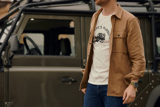 Knickerbocker x Gear Patrol Overland T-Shirt - image of a man, standing in front of a green Land Rover, wearing the Overland tee shirt under a brown overshirt