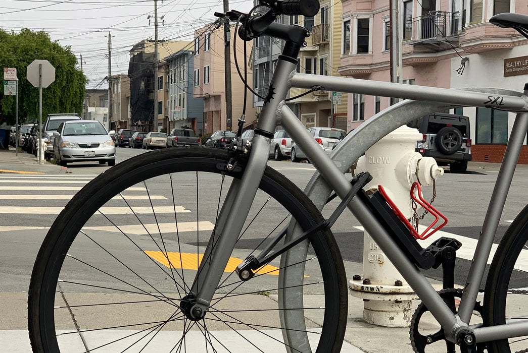 Lobster Lock Folding Bike Lock - image of a silver bike in a city scene with a lock affixed to it
