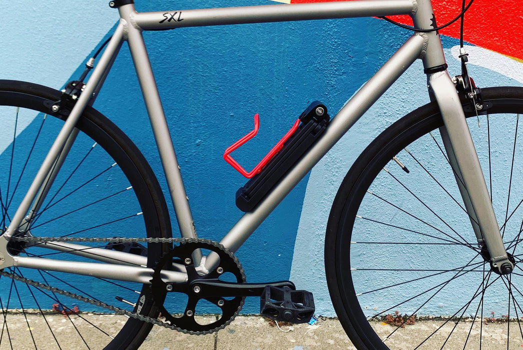 Lobster Lock Folding Bike Lock - image of lock attached to a silver bicycle, standing in front of a blue painted wall