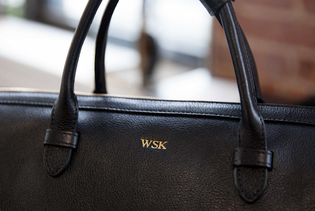 Image of gold monogram lettering on a black leather bag