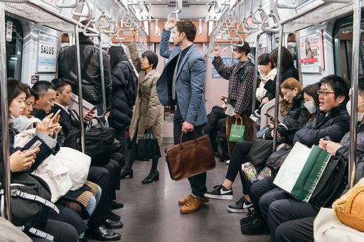 Lotuff Leather Zip-Top Briefcase - Chestnut - Man holding the briefcase by its top handle while standing on a subway