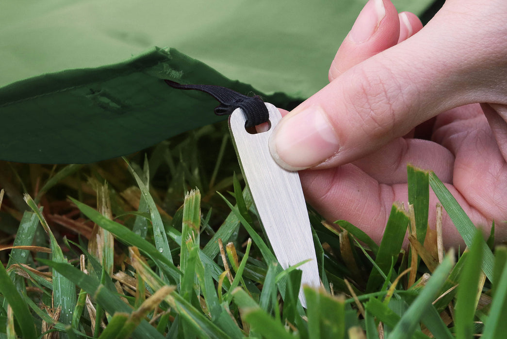 Matador Packable Pocket Blanket - Black - Close-up of a person using a stake to anchor the blanket in grass