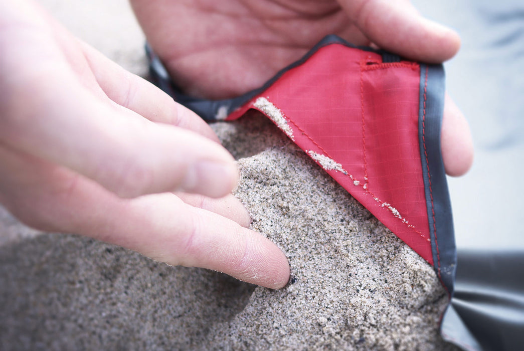 Matador Packable Pocket Blanket - Red - Close-up of a person using sand to weigh down a corner of the blanket at the beach