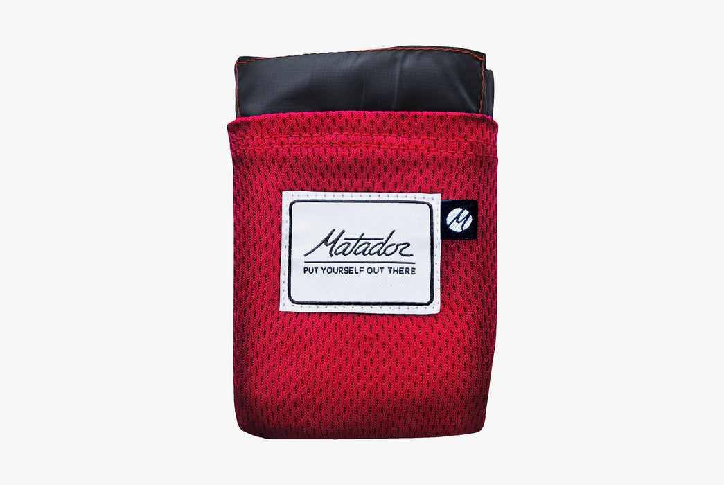 Matador Packable Pocket Blanket - Red - Front view of folded-up blanket in case