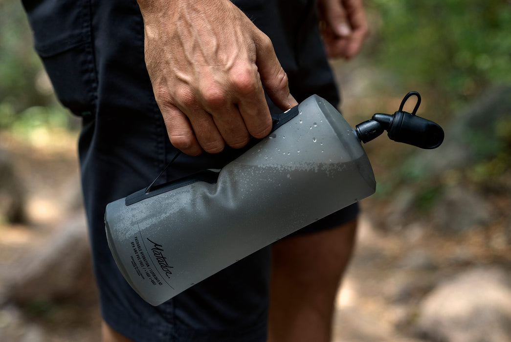 Matador Packable Water Bottle - Close-up of man holding the water bottle by its side handle