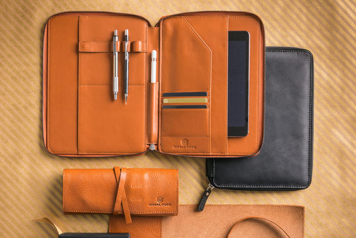 Moral Code Shorthand Portfolio - Brown - laying open next to other leather goods holding cards, pens, and an iPad.