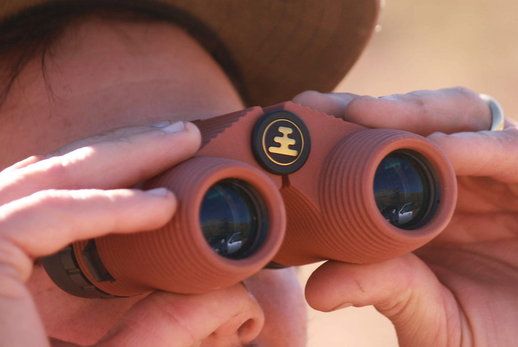 "Nocs Standard Issue 8x25 Waterproof Binoculars - ""Flat Earth"" (Orange) - close-up view of man looking through binoculars"