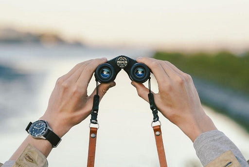 Nocs Standard Issue 8x25 Waterproof Binoculars - Black - man holding binoculars in front of a blurred out nature scene
