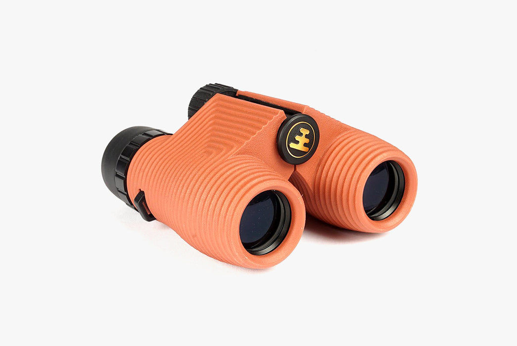 "Nocs Standard Issue 8x25 Waterproof Binoculars - ""Flat Earth"" (Orange) - side view of binoculars showing grooved detailing"