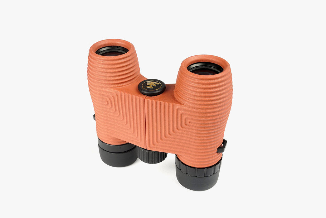 "Nocs Standard Issue 8x25 Waterproof Binoculars - ""Flat Earth"" (Orange) - binoculars standing up, lens-side down"