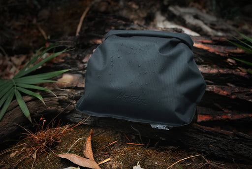 Matador FlatPak Toiletry Case - Black - Case laying on a forest floor, showing droplets of water on the case