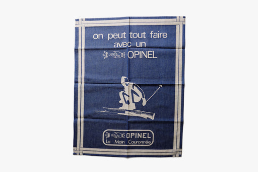 Opinel Kitchen towel - On Peut Tout Faire - Blue - Unfolded towel with French words and an illustration of a man skiing