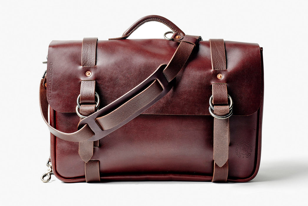Orox Leather Co. Nuntius X Briefcase - Brown - front view of bag standing up with strap draped over top of bag