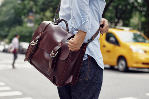 Orox Leather Co. Nuntius X Briefcase - Brown - man wearing the bag and holding onto it as he crosses the street