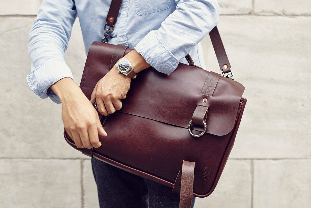 Orox Leather Co. Nuntius X Briefcase - Brown - front view of man wearing the bag and closing it