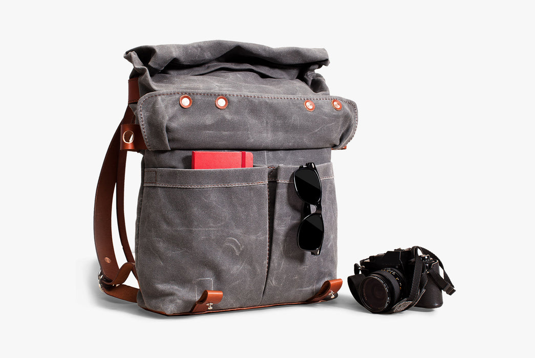Orox Leather Co. Parva Rucksack - Gray - diagonal view of bag standing up with a notebook and sunglasses in the front pockets