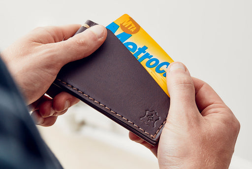 Orox Leather Co. Slim Cardholder - Brown - man taking a MetroCard out of the cardholder