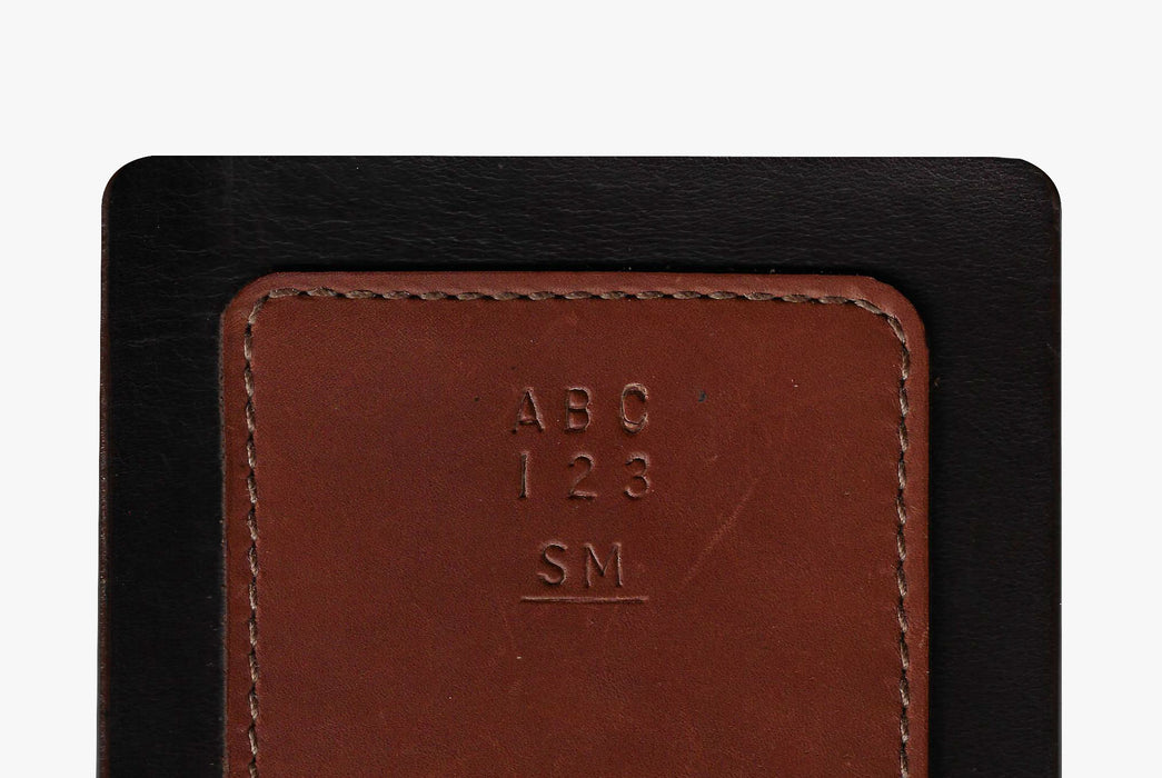 Brown Orox Leather Co. Arida Classic Card Case - close-up shot of letters and numbers imprinted in leather