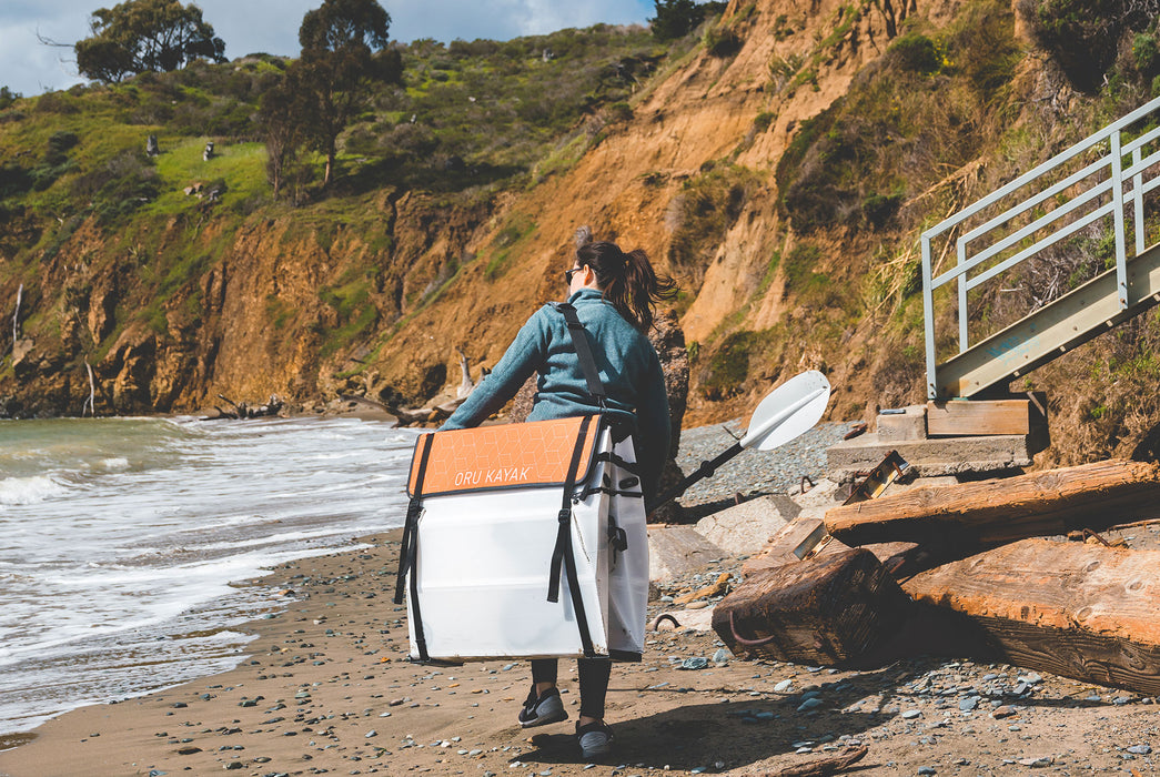 Oru Kayak - Beach LT - Woman carrying folded up kayak as she walks toward the water