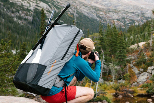 Oru Kayak - Pack Bag - A man wearing the pack bag as a backpack as he photographs a mountainous landscape