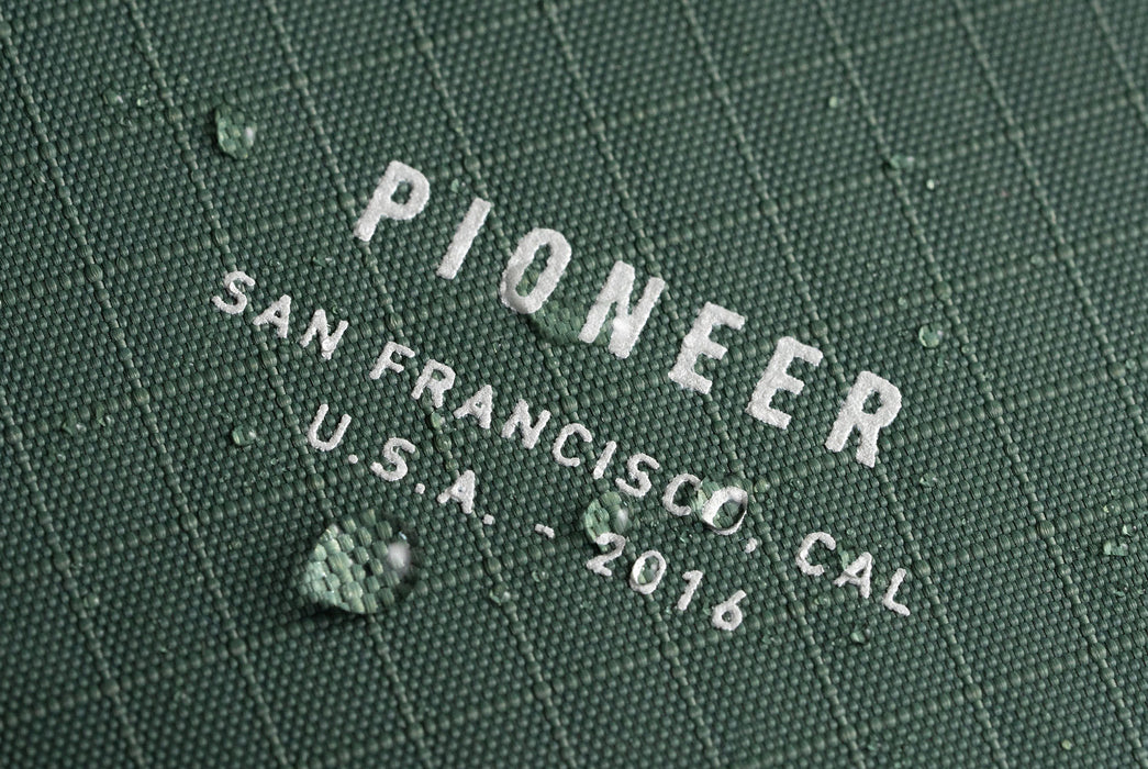 Evergreen - Pioneer Flyfold Wallet - Close up on logo with beading water