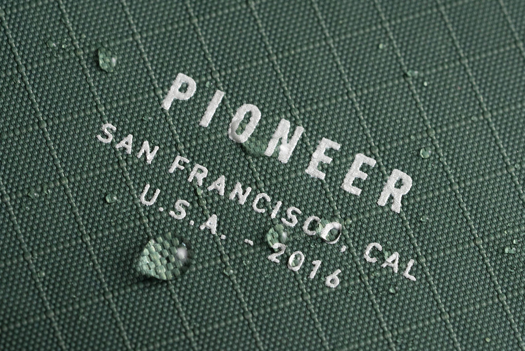 Evergreen - Pioneer Matter Bifold Wallet - Close up of logo with beading water